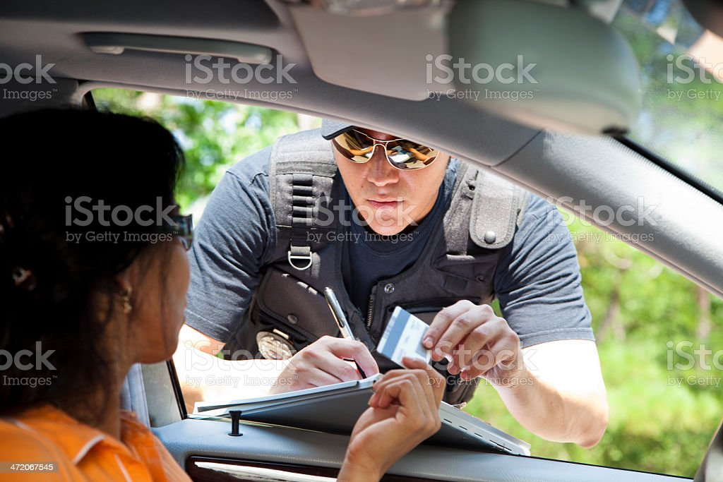Crime: Policeman gives driver a traffic ticket. stock photo