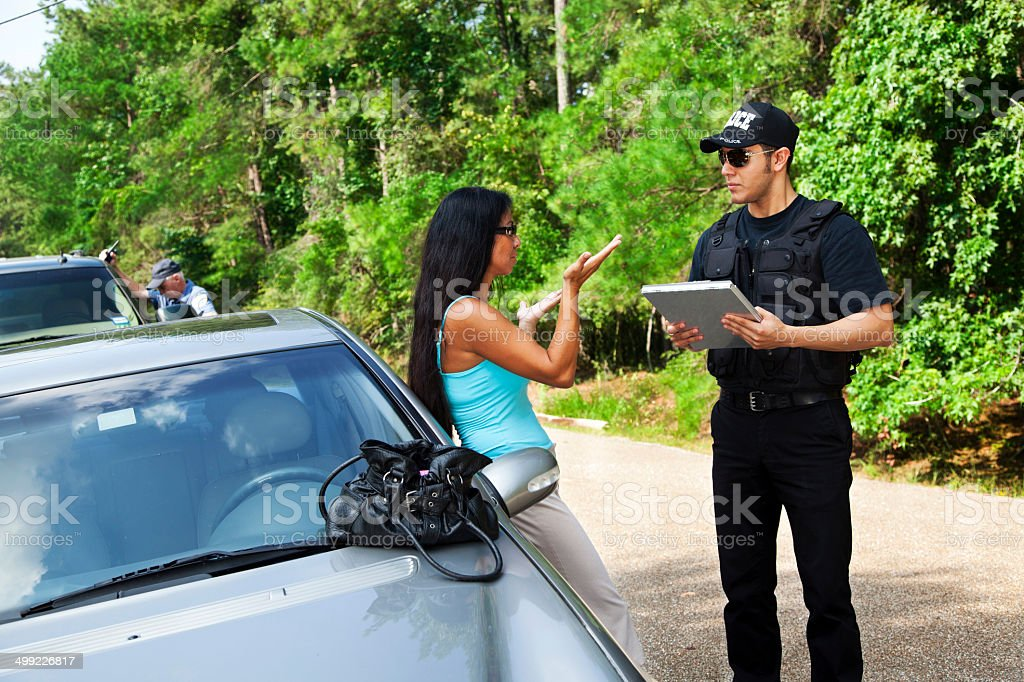 Crime: Policeman makes traffic stop. Woman explaining. Officer background. stock photo