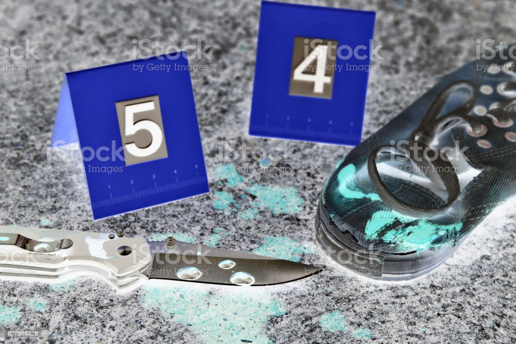 Crime scene investigation, Bloody knife and victim's shoes with criminal markers on ground, Homicide evidence. stock photo
