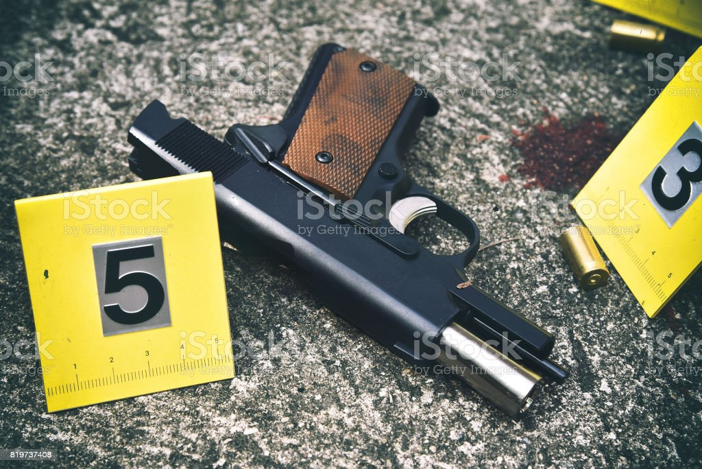 Crime scene investigation, Pistol and bullet shell with blood stain against the crime marker on the ground. stock photo