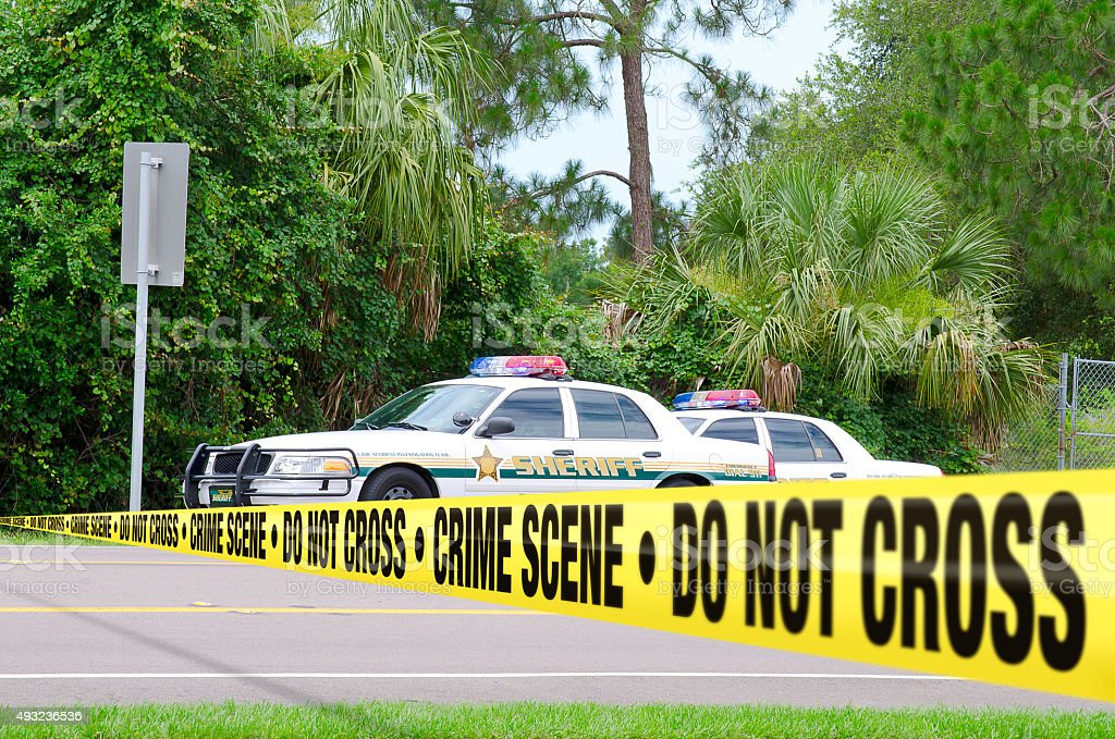 Crime scene investigation w sheriff cars and barrier tape stock photo