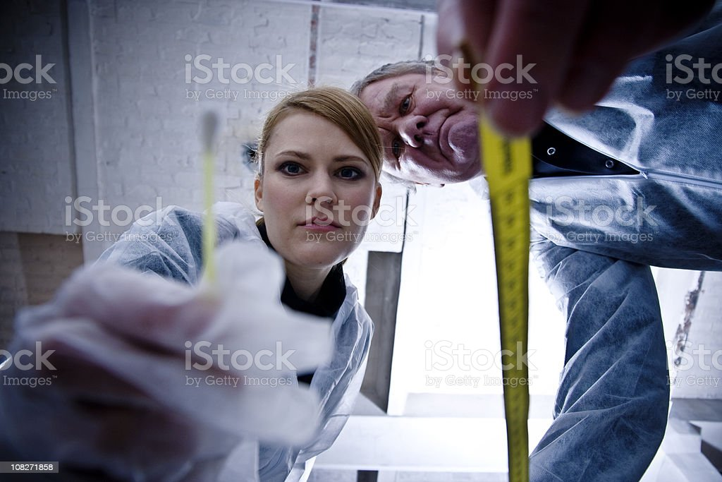 Crime Scene Investigation with Detective Inspecting Body stock photo