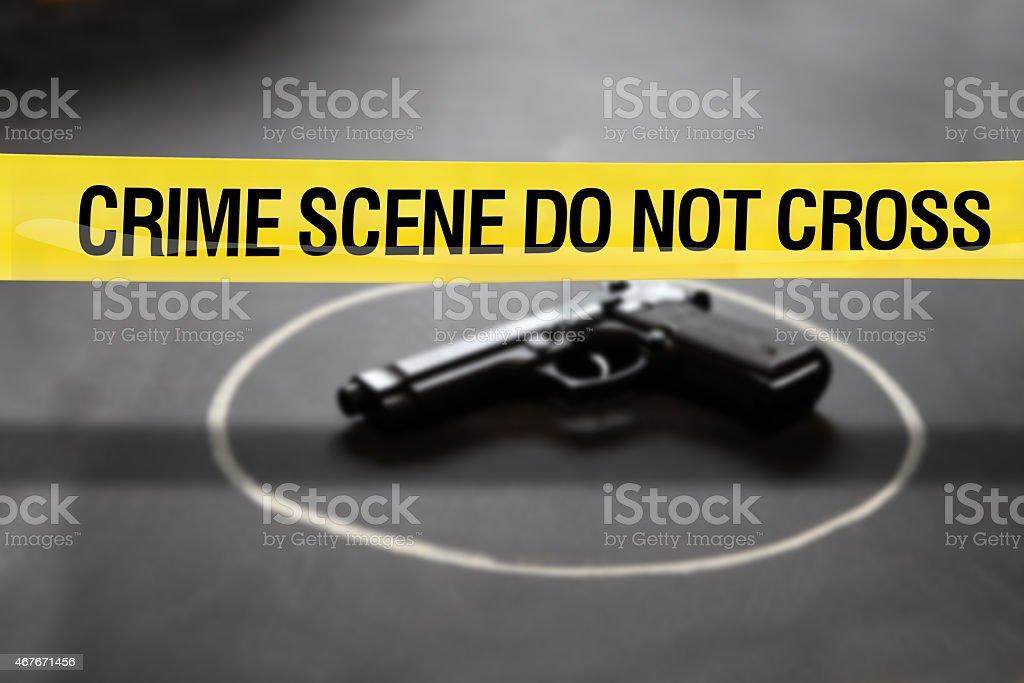 Crime scene, police yellow tape and gun on dark floor stock photo