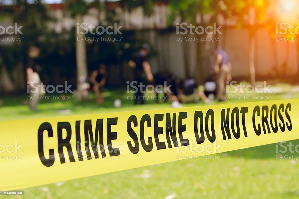 crime scene tape and blurred law enforcement team background stock photo