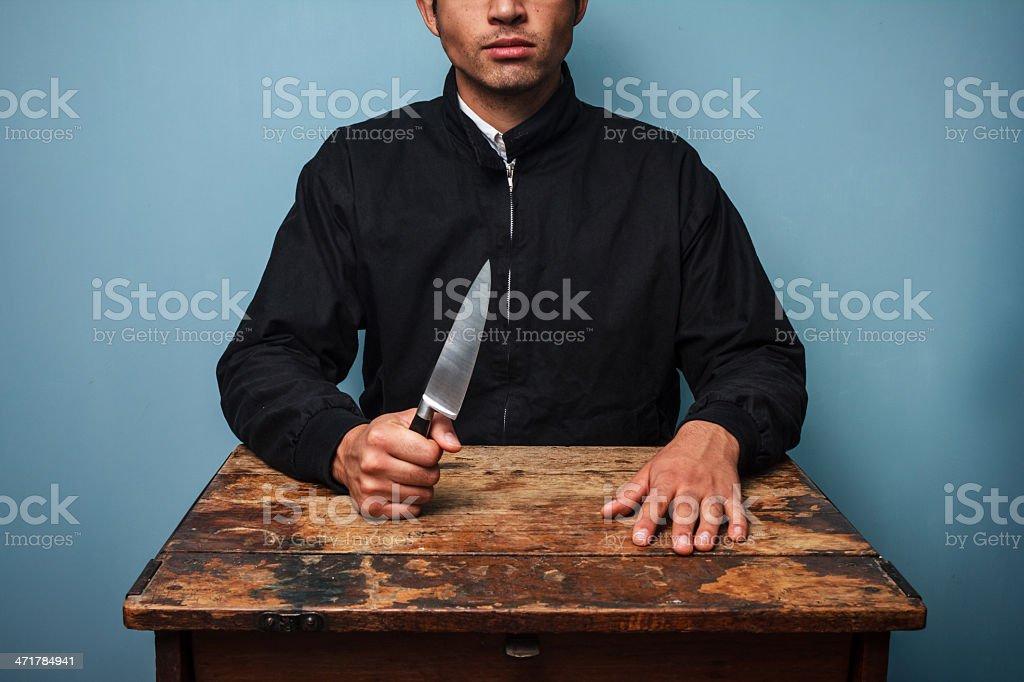 Criminal at table waving a knife royalty-free stock photo