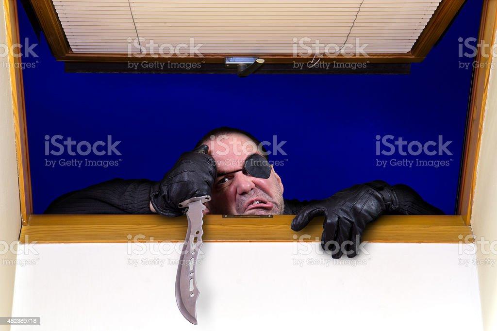 criminal climbs through the window stock photo