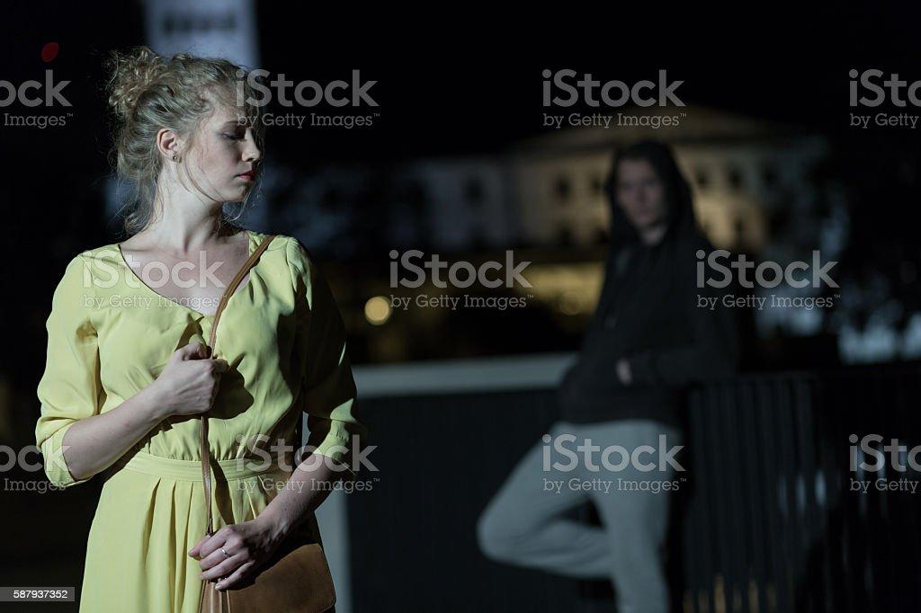 Criminal following young woman stock photo
