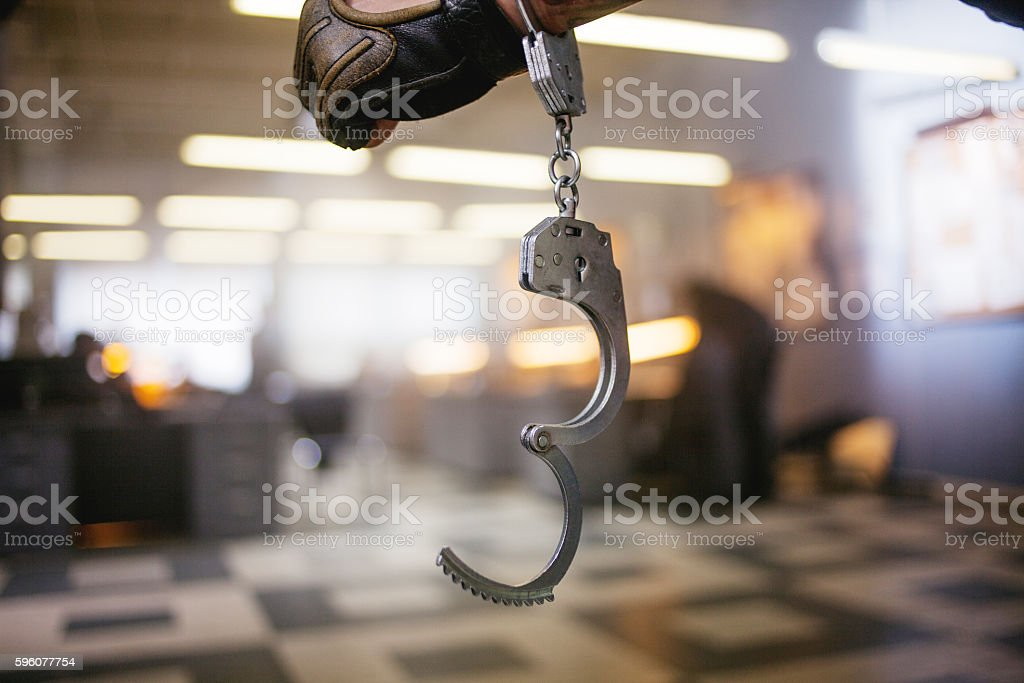 Criminal man. Hand male in unbuttoned handcuffs, on background of stock photo