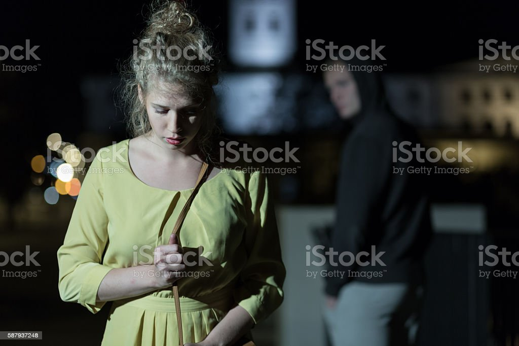 Criminal observing young woman stock photo