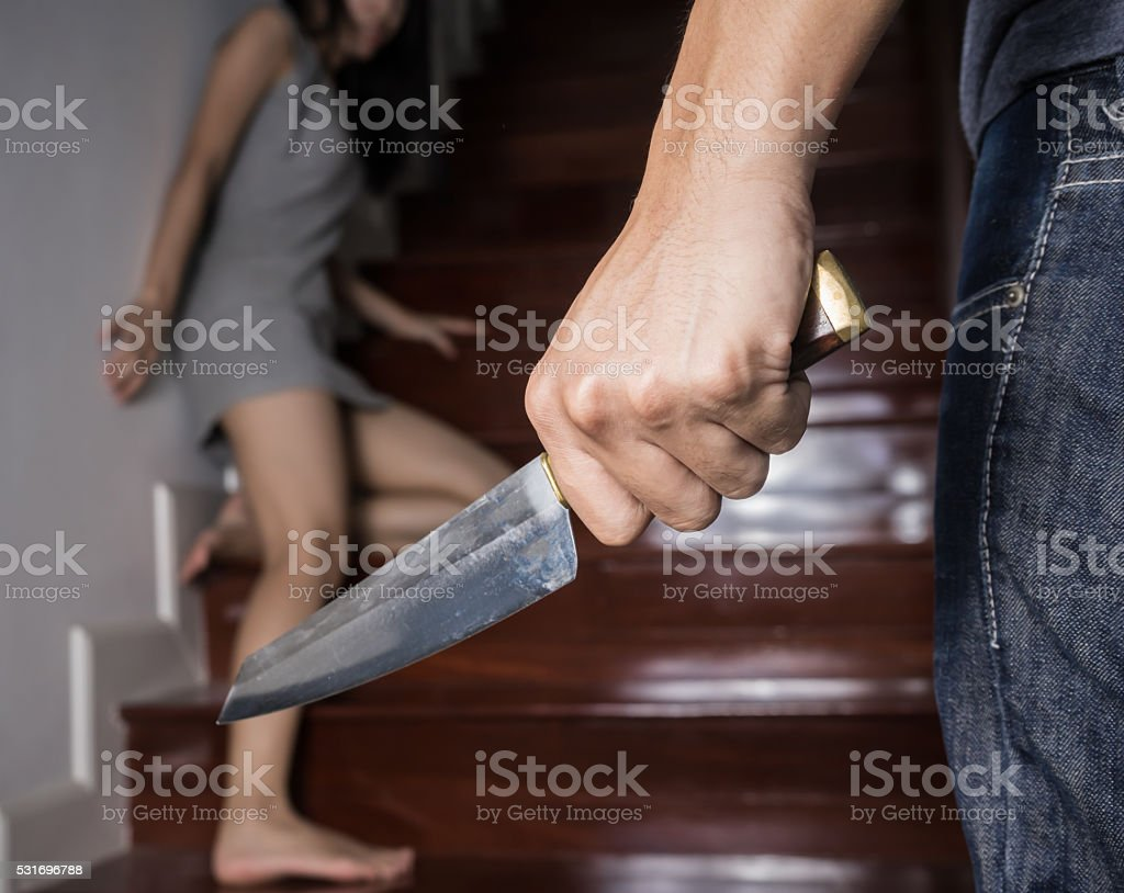 Criminal with Knife attack woman in a house,focus hand stock photo