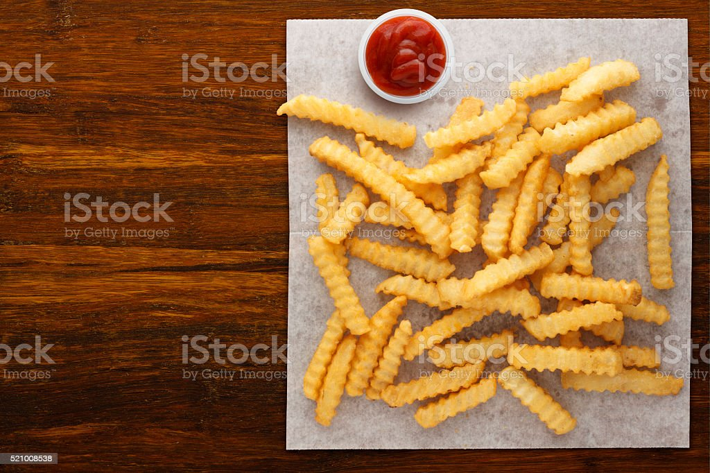 Crinkle Cut Fries on Wax Paper with Ketchup stock photo