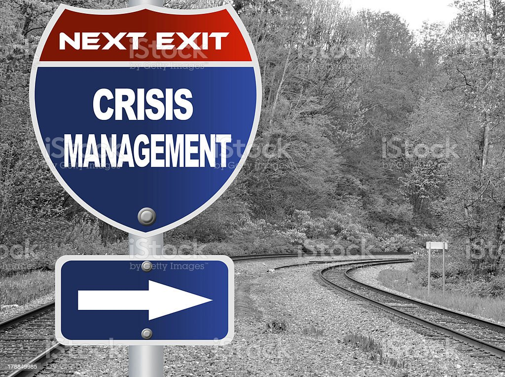 Crisis management road sign and a grey train tracks royalty-free stock photo
