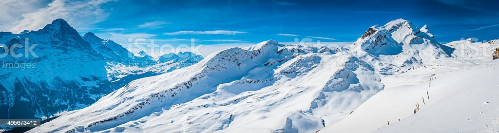 Crisp white snow on mountain peaks panorama skiing Alps Switzerland stock photo