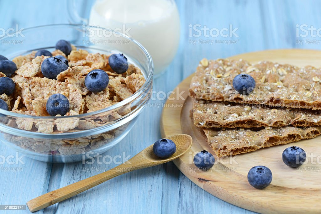 Crispbread and cereal with blueberry and milk on a wooden background stock photo