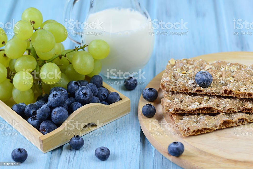 Crispbread with blueberry, grapes and milk on a wooden background stock photo