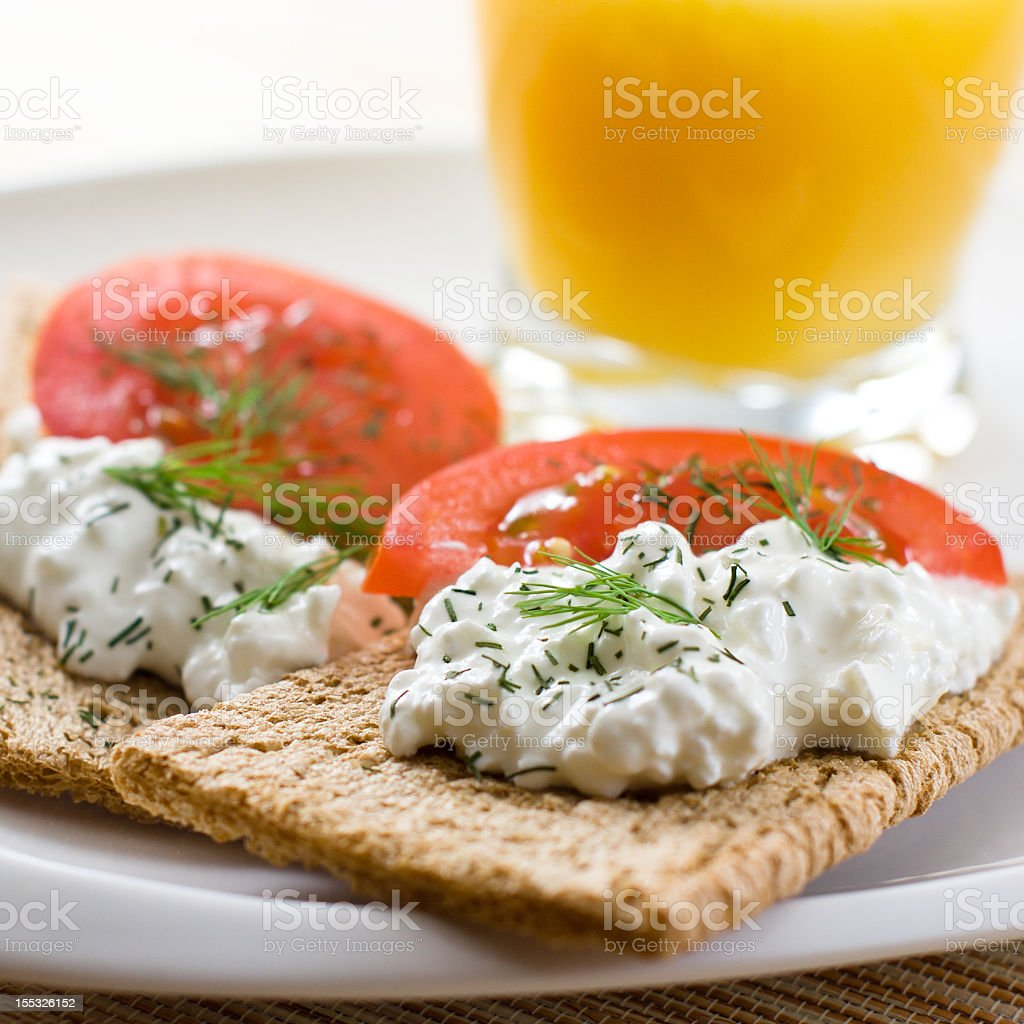 Crispbread with fresh cheese and tomato stock photo