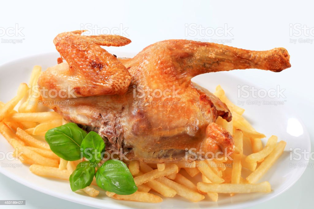 Crisp-skinned chicken with French fries royalty-free stock photo