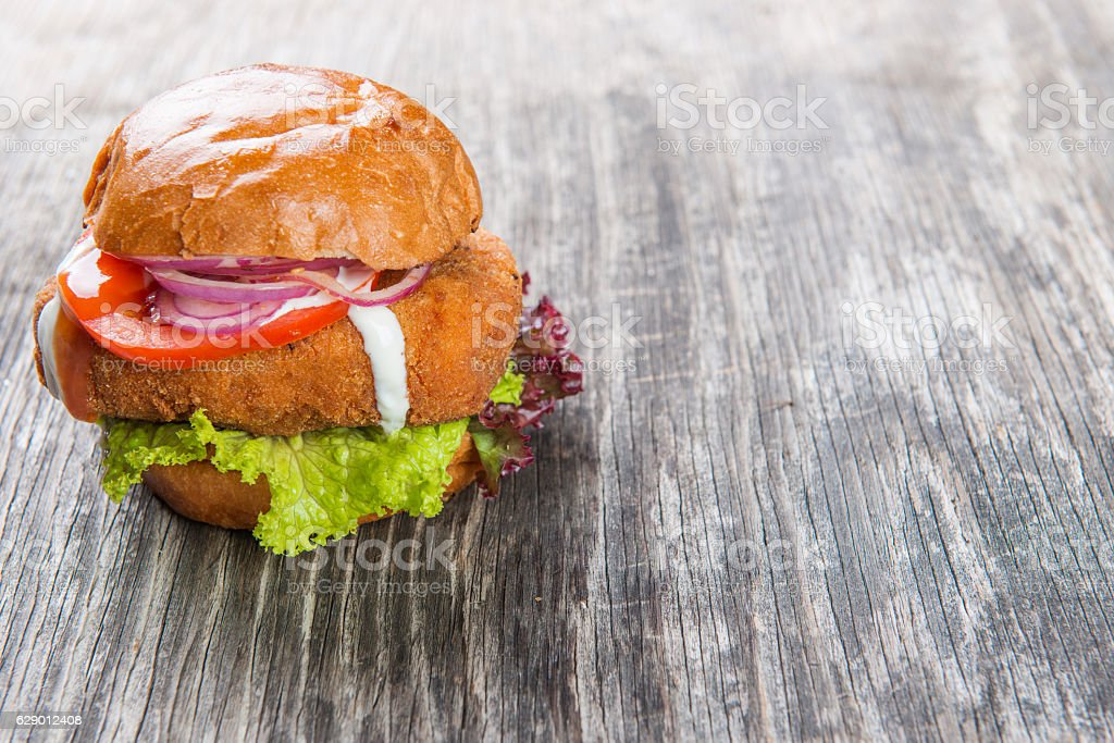 Crispy chicken burger on rustic background and copy space stock photo