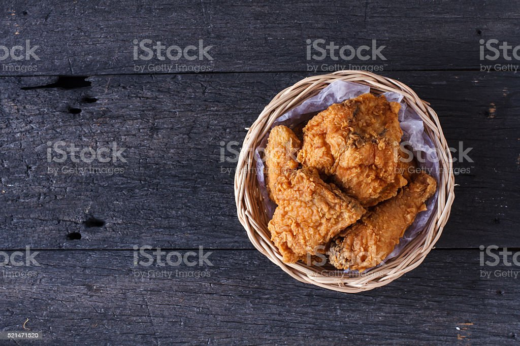 Crispy fried chicken in a basket on wooden table.Top view stock photo