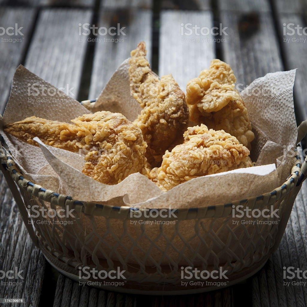 Crispy fried chicken in basket on wooden floor stock photo