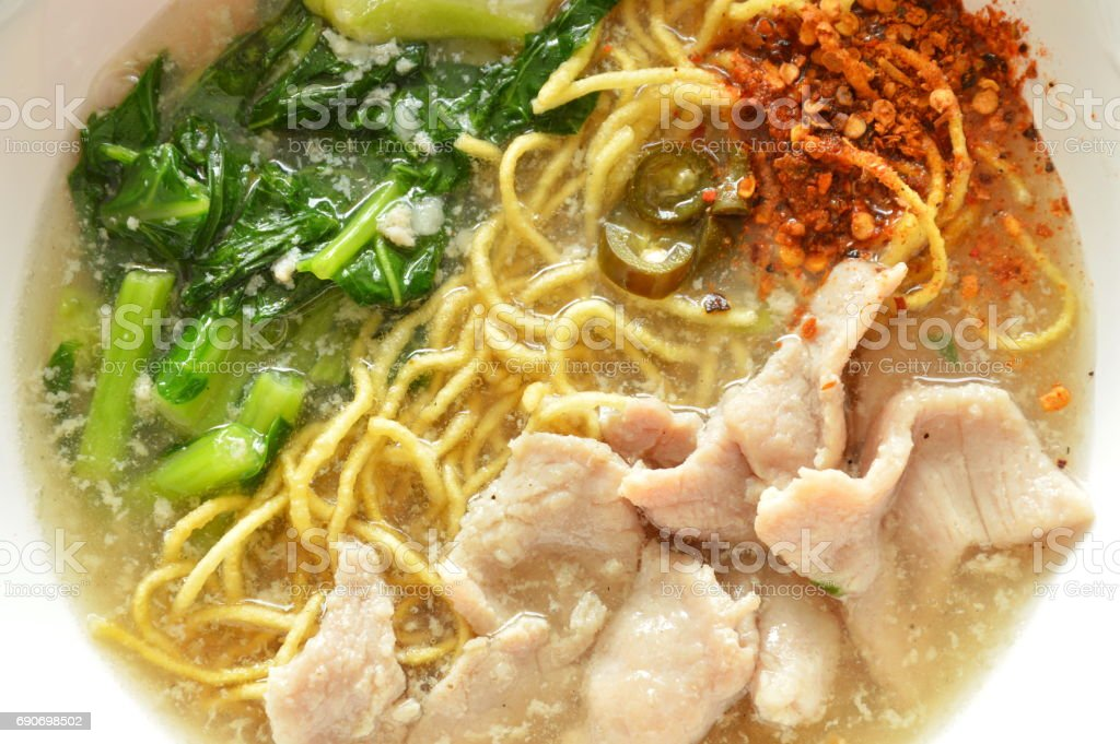 crispy fried egg noodle with pork and kale in gravy sauce stock photo