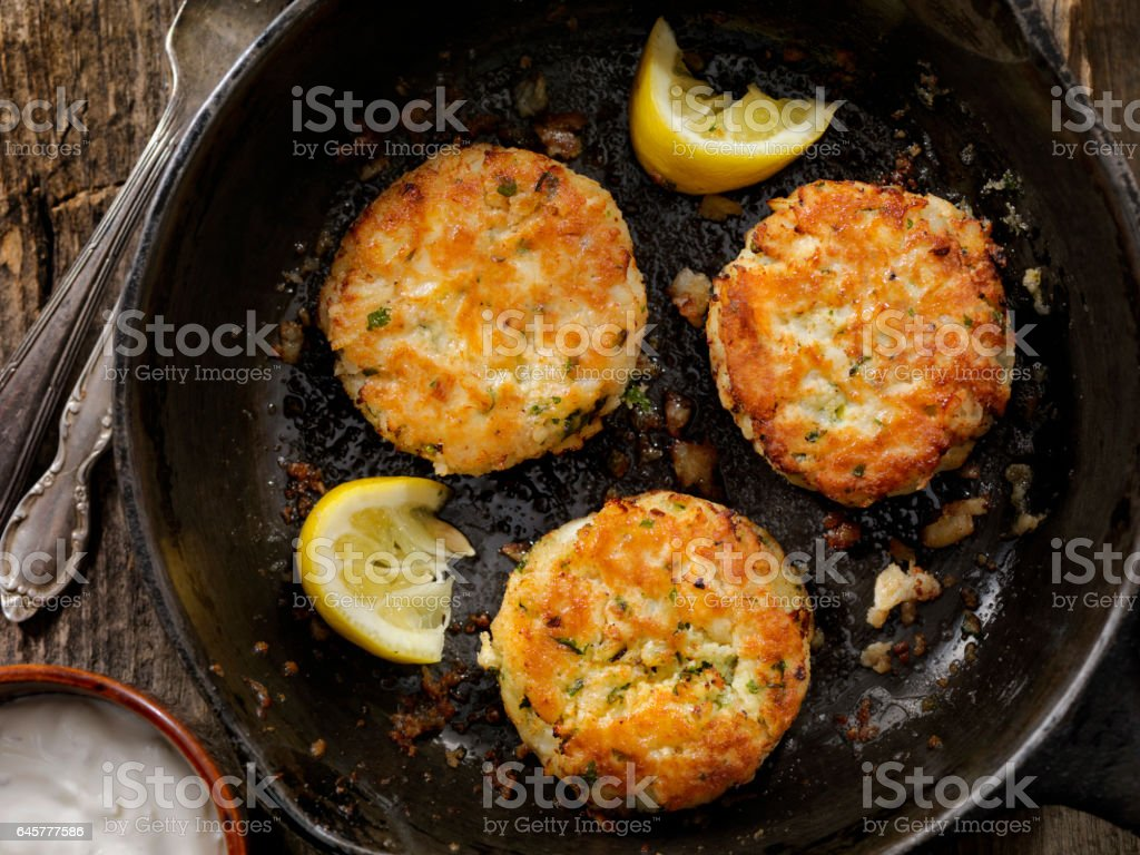 Crispy Golden Fish Cakes in a Cast Iron Skillet stock photo