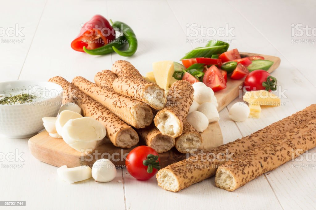 Crispy grissini (bread stick), variety of cheese,mint and yogurt dipping sauce and fresh vegetables stock photo