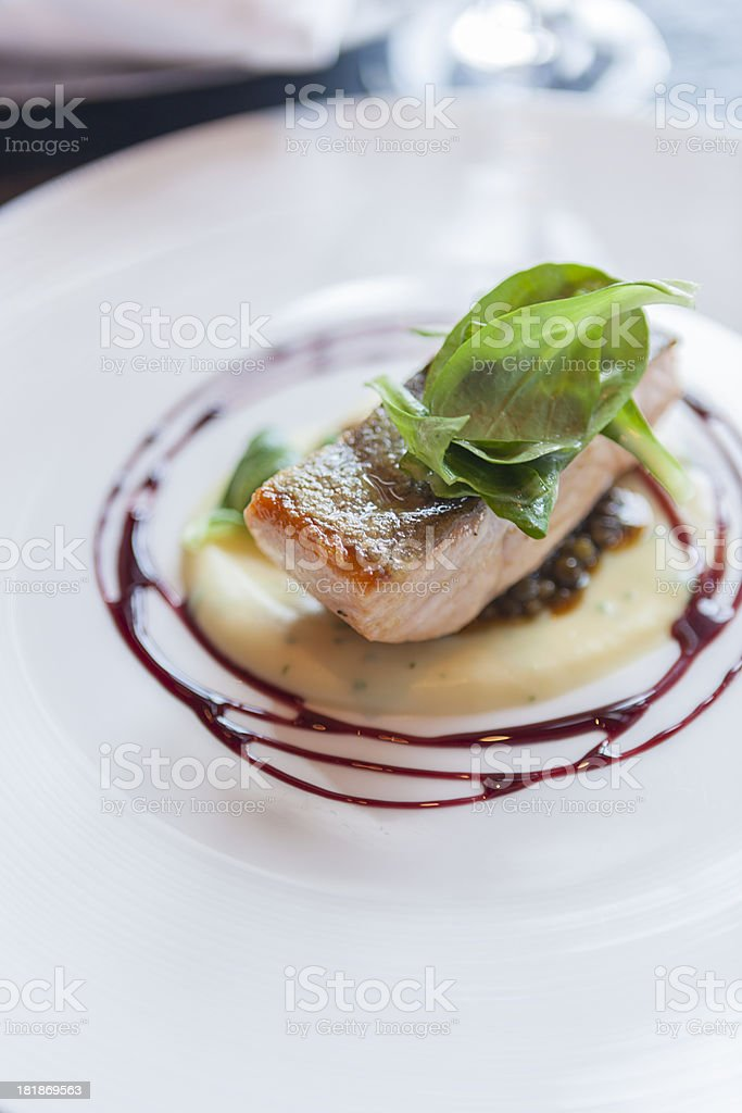 Crispy skin salmon with parsnip puree, lentils and wine sauce stock photo