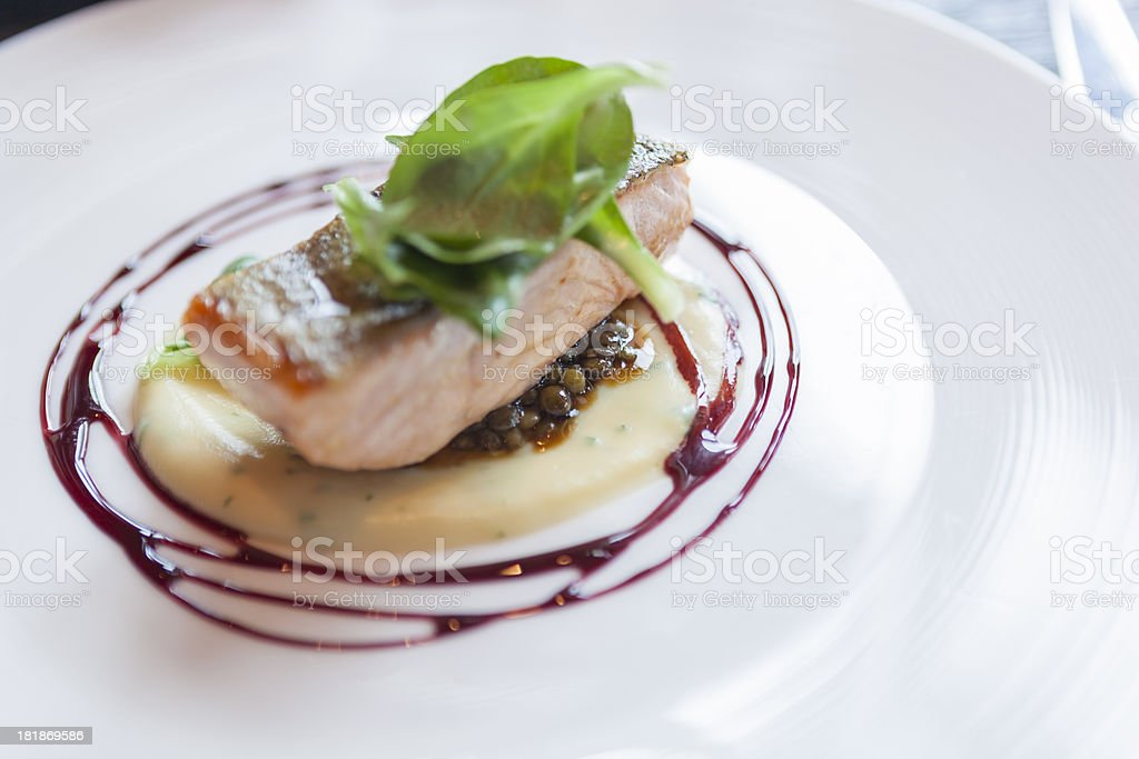 Crispy skin salmon with parsnip puree, lentils and wine sauce stock photo