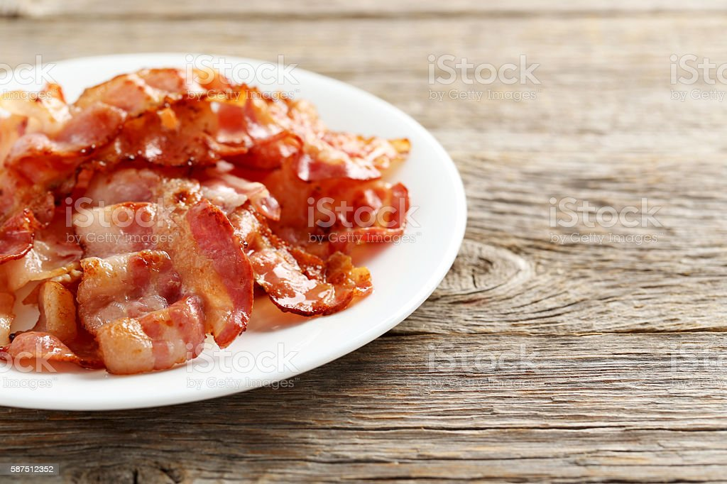 Crispy strips of bacon on a grey wooden background stock photo