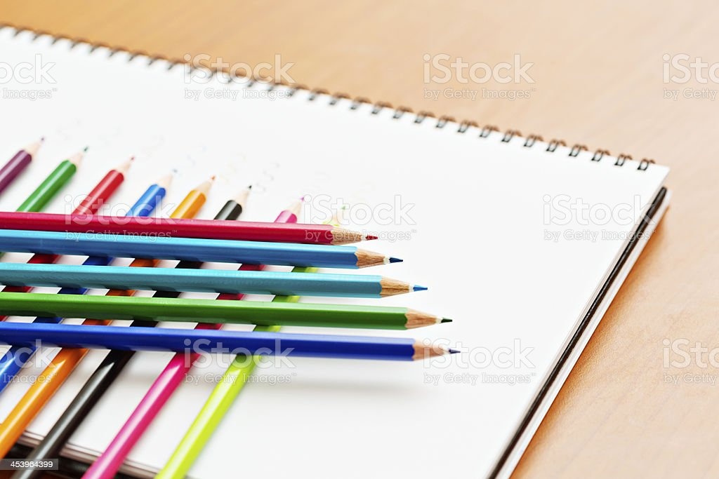 Criss-cross stack of pencil crayons on spiral-bound sketchbook royalty-free stock photo