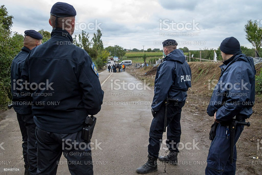 Croatian policemen watching refugees entering Croatia from Serbia stock photo