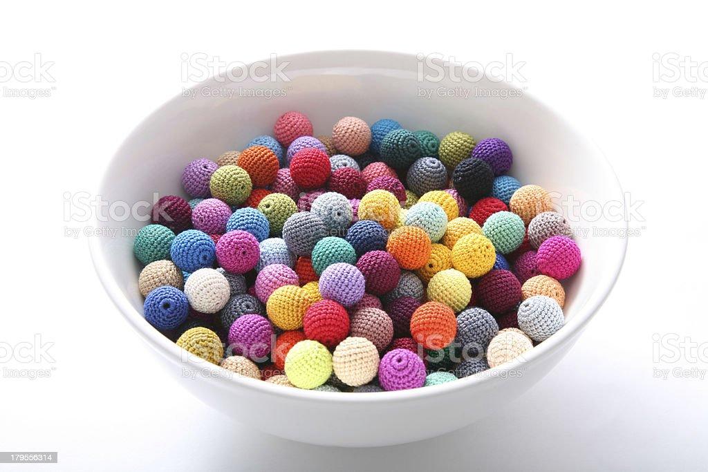 Crochet beads balls in white bowl royalty-free stock photo