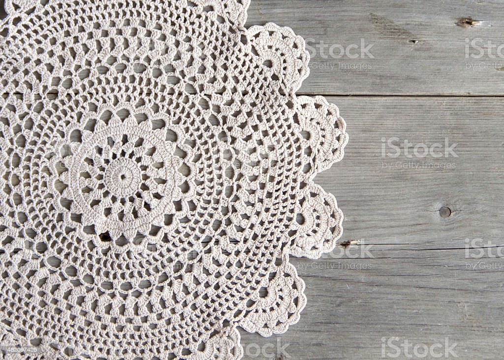 Crochet doily over old grey wood stock photo