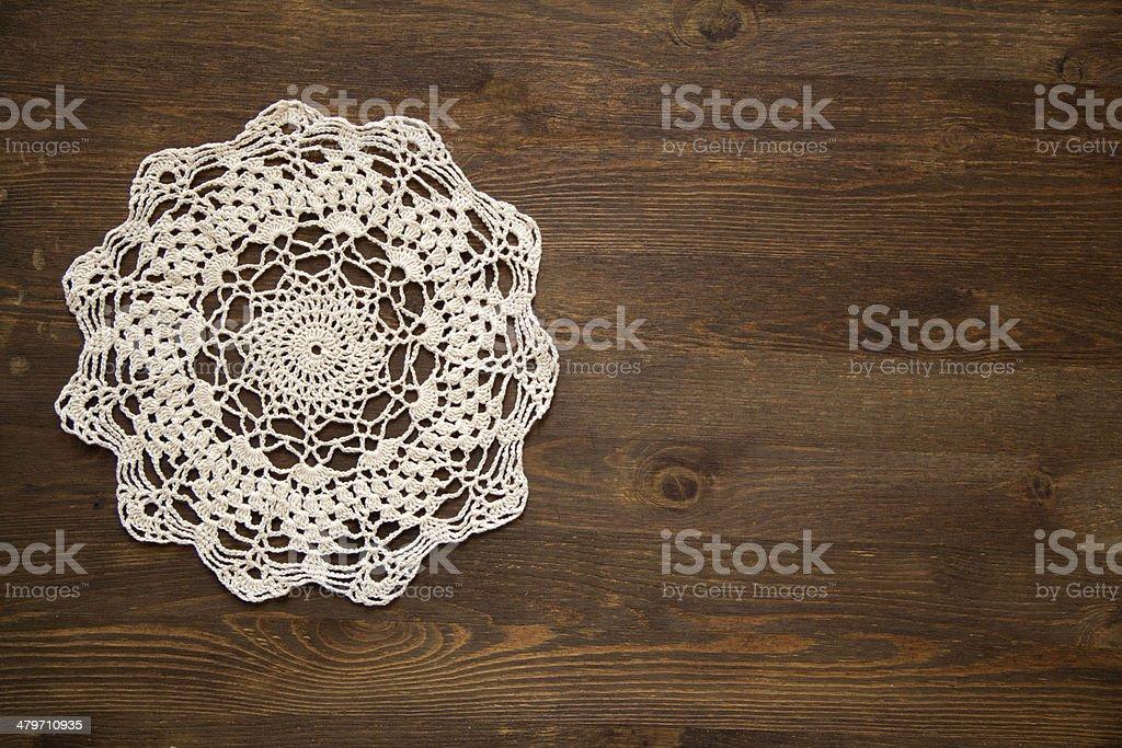 Crochet doily overdark wood stock photo