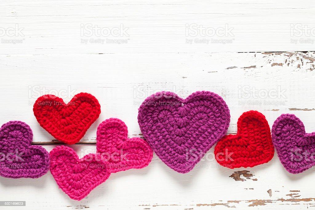 Crochet hearts on white table stock photo