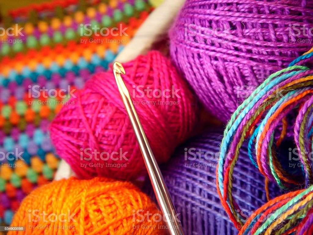 Crochet hook and balls of colored thread stock photo