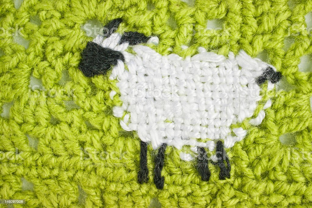 Crochet pattern lamb (sheep) in green field stock photo