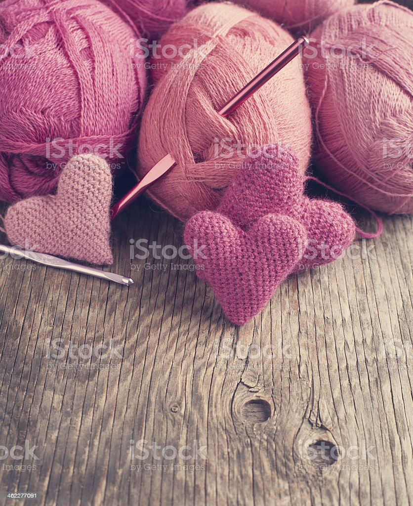 Crochet pink hearts  and yarn on wooden background. stock photo