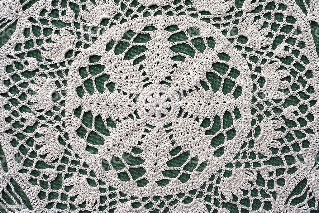Crocheted Doily on Green Fabric stock photo