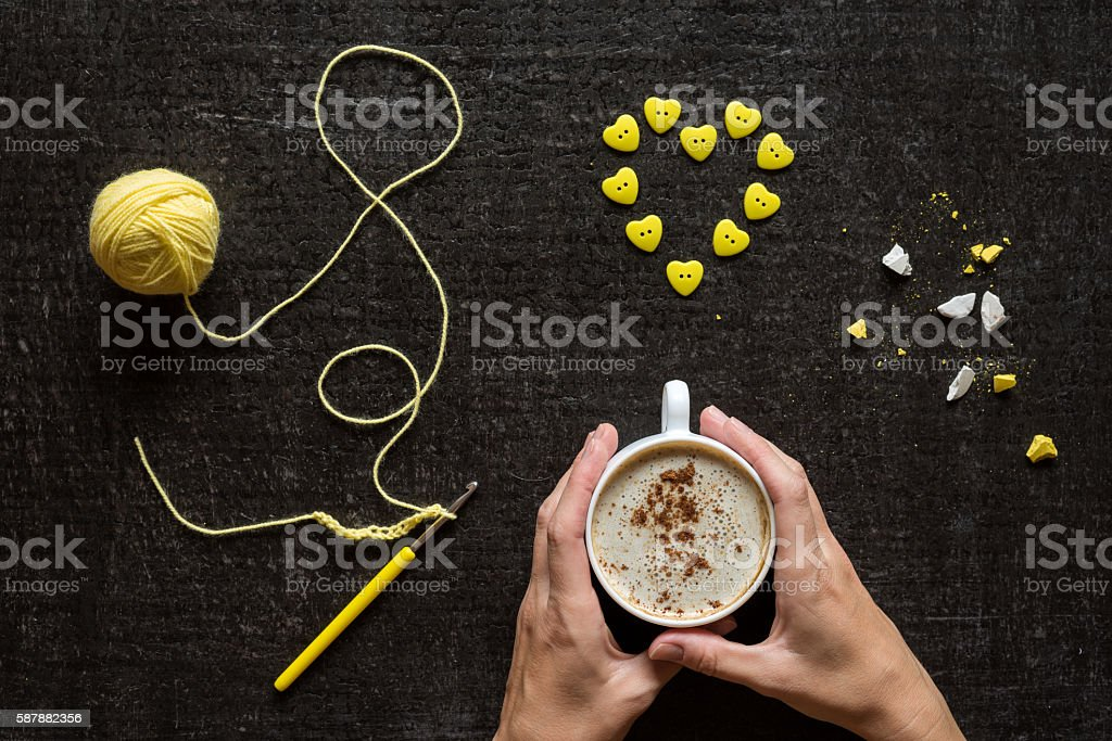 Crocheting, button heart and hands with coffee stock photo