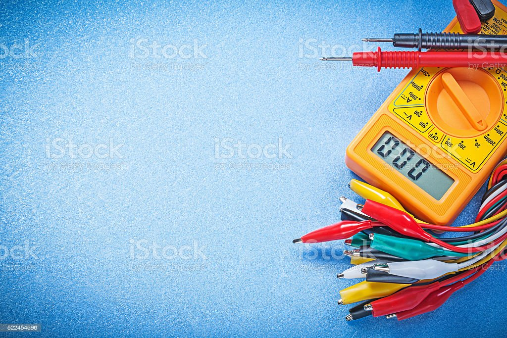 Crocodile plugs electric digital multimeter on blue background e stock photo