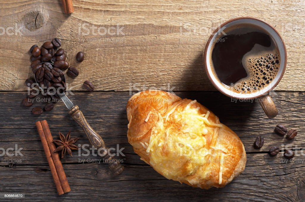 Croissant with cheese and cup of hot coffee on old wooden background,...