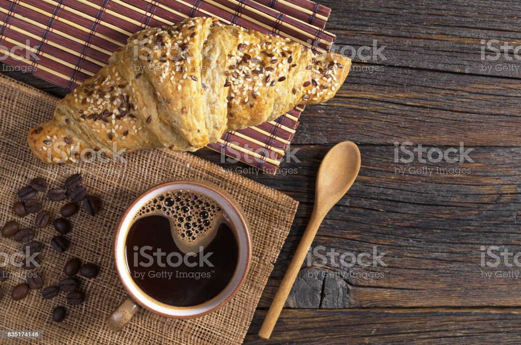 Croissant with flax seeds and cup of hot coffee on old wooden table,...