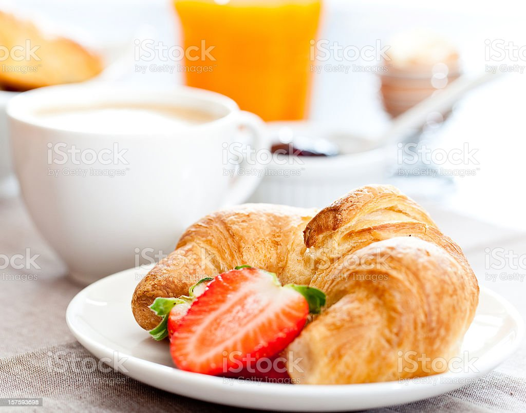 Croissant and sliced strawberry on a plate in front of mug royalty-free stock photo