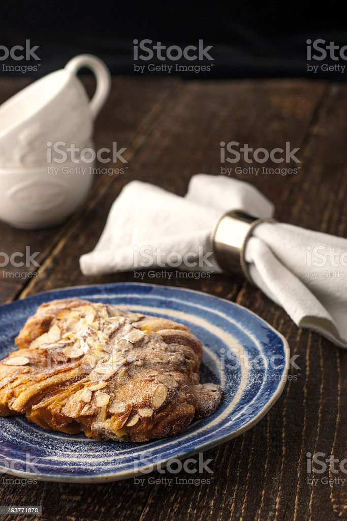 Croissant on ceramic plate with blurred cups and napkin stock photo