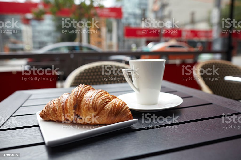 Croissant pastry with coffee cup on table outdoors street view royalty-free stock photo