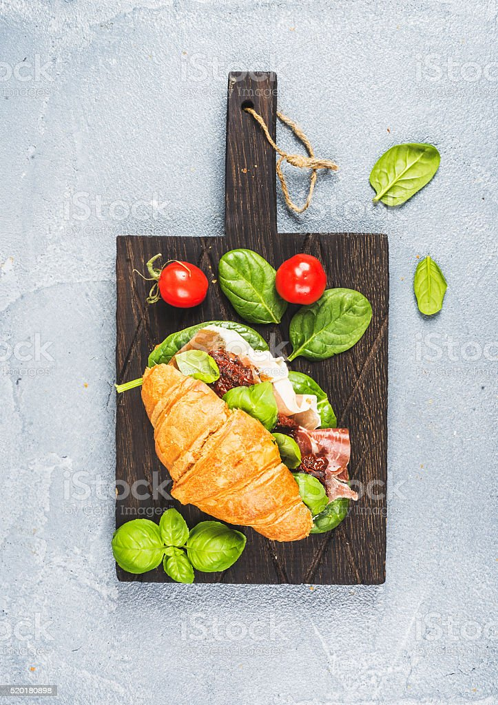 Croissant sandwich with smoked meat Prosciutto di Parma, sun dried stock photo