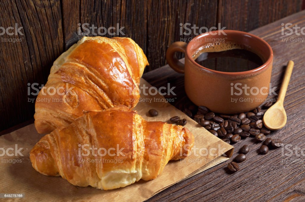Freshly baked croissants and cup of hot coffee on dark wooden table