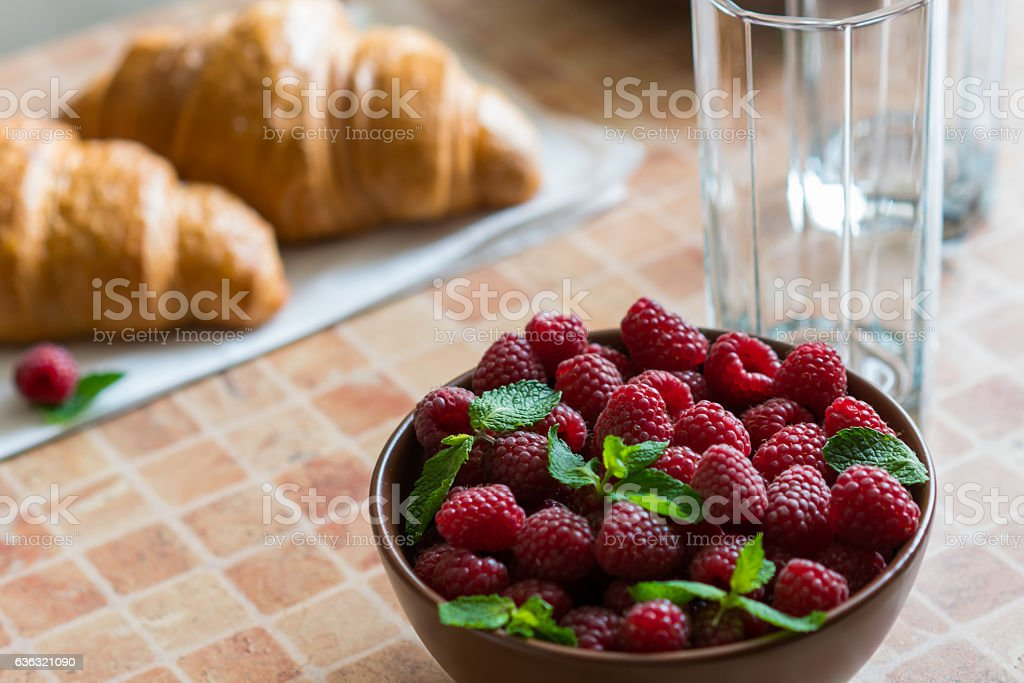 Croissants and raspberries on the table. stock photo